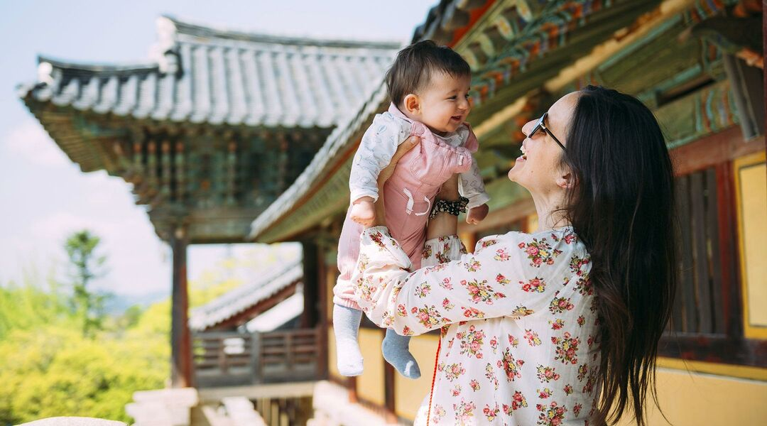 mom lifting baby into the air while traveling in country with asian temple