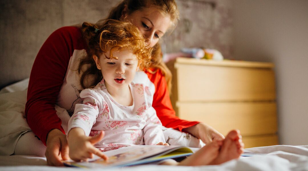 mom reading to toddler in bed