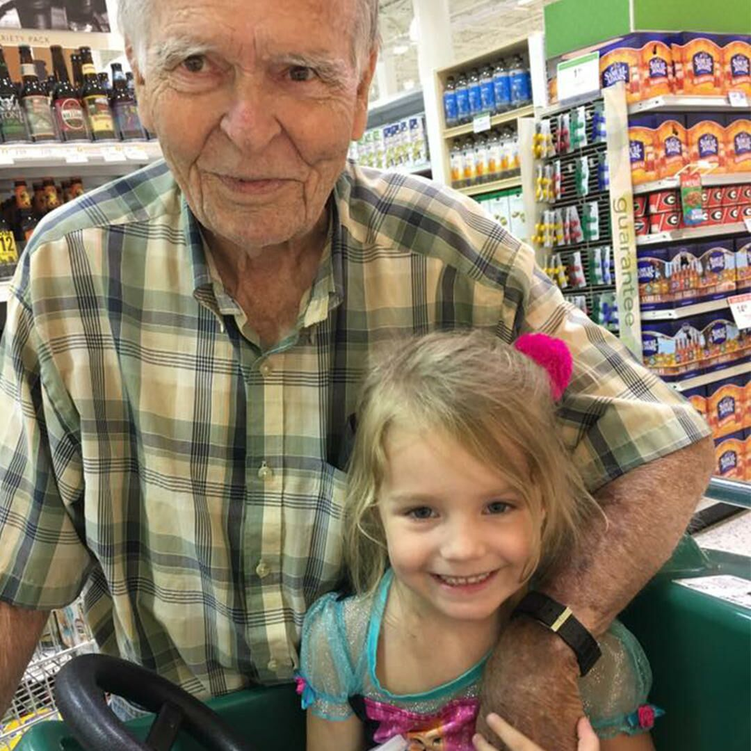 4-year-old Norah Wood poses with an elderly man, Dan Peterson, in the grocery store.
