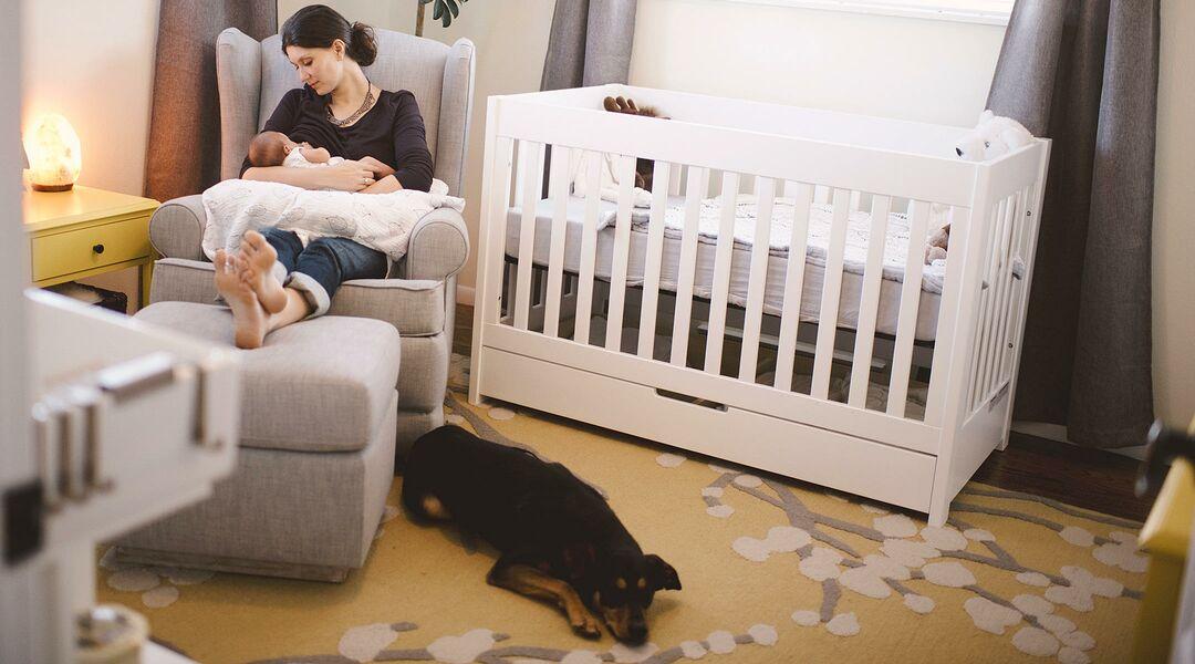 new mom breastfeeding newborn baby in nursery