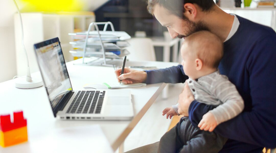 Dad working at computer with baby