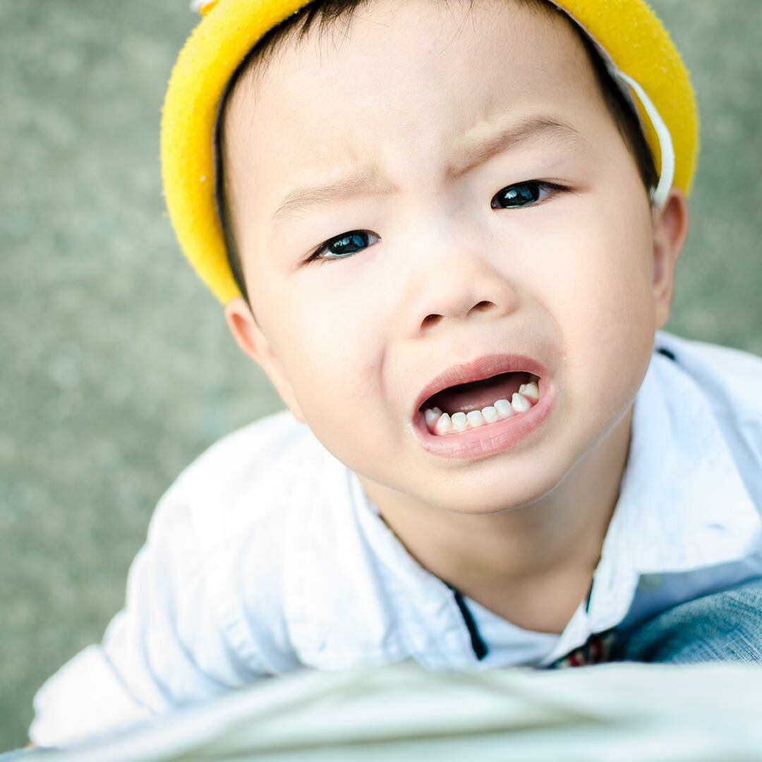 Closeup of an Asian child starting to have a temper tantrum.