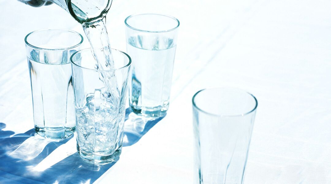 water pitcher pouring water into glasses