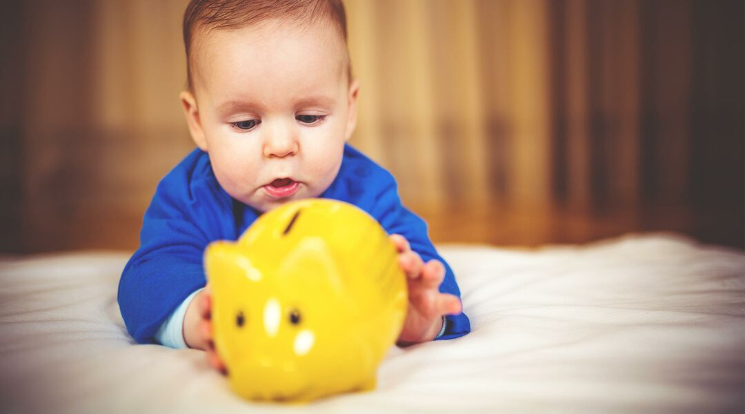 Baby playing with yellow piggy bank