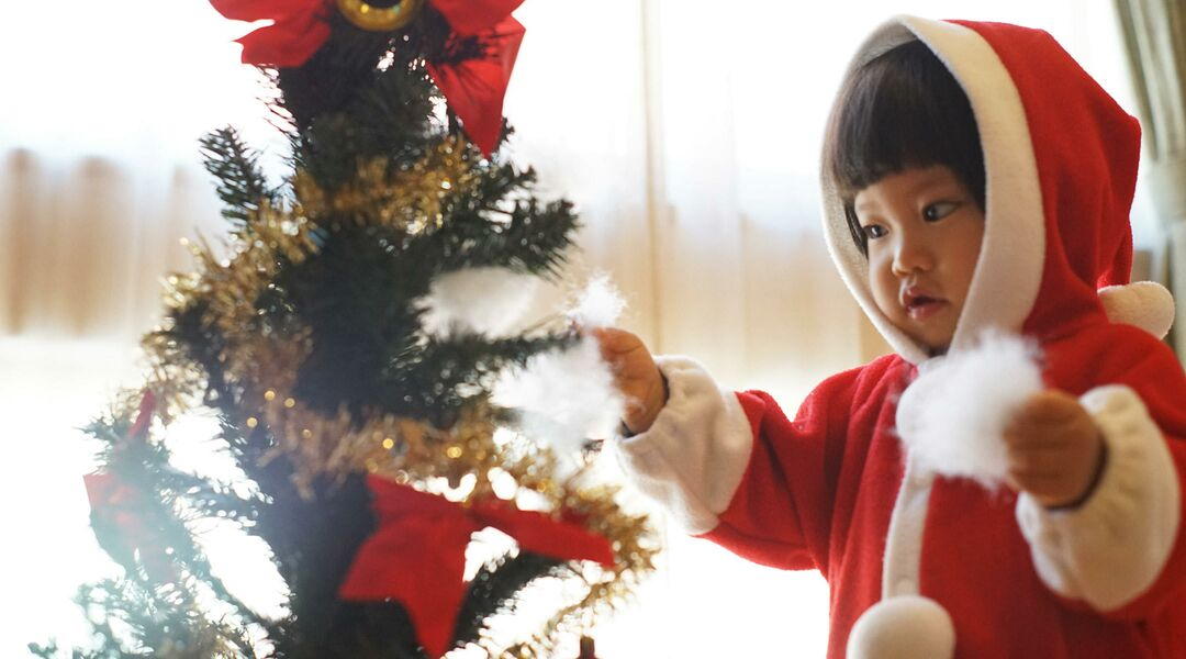 Little girl in santa outfit decorating tree