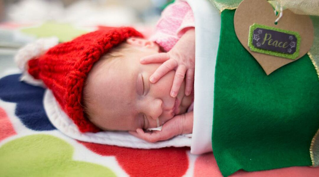 Santa looking down at a smiling preemie dressed as a gift