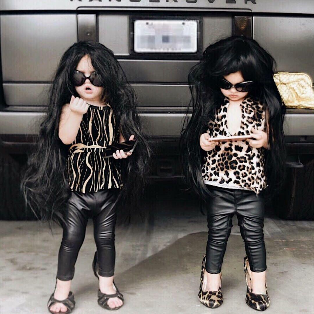 Twin toddler girls dressed up as the Kardashians.