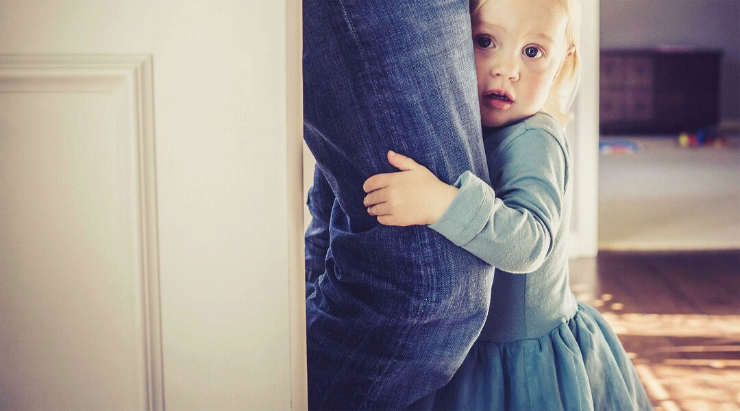 little girl separation anxiety holding parent leg