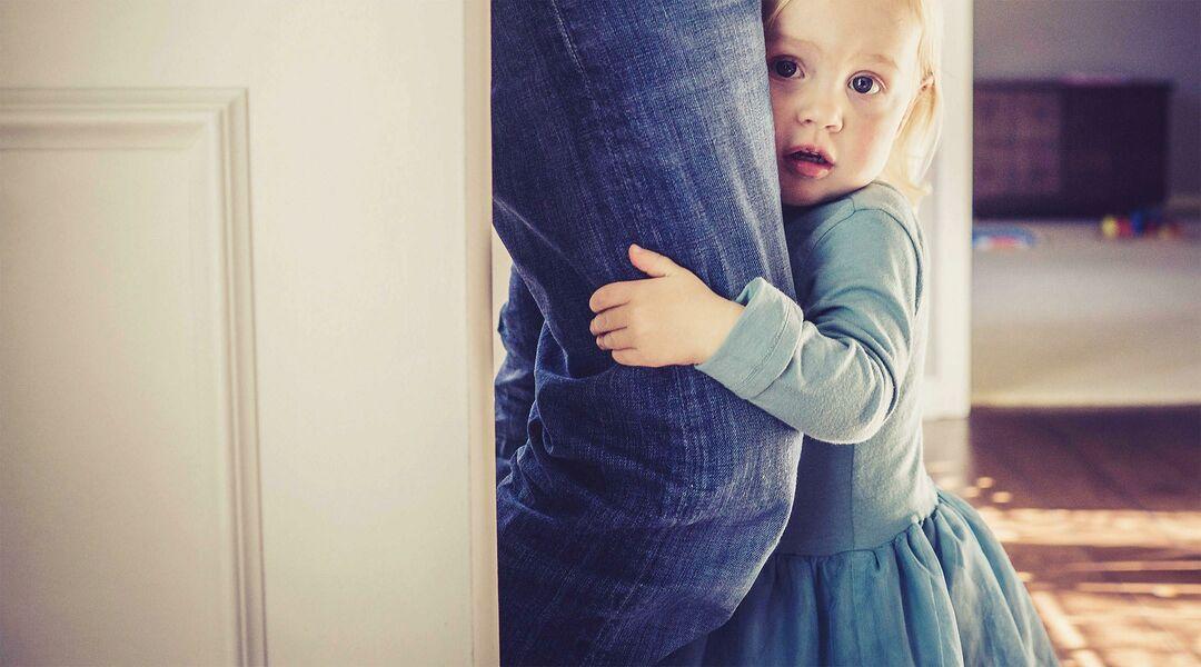 little girl separation anxiety holding parent leg