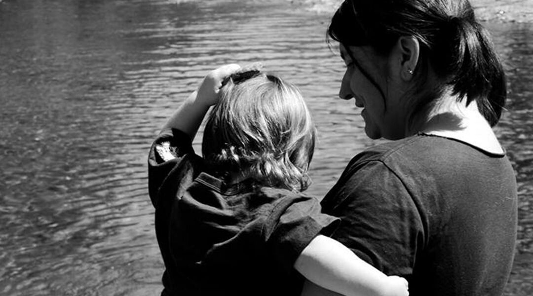 Black and white photo of mom holding toddler by a body of water