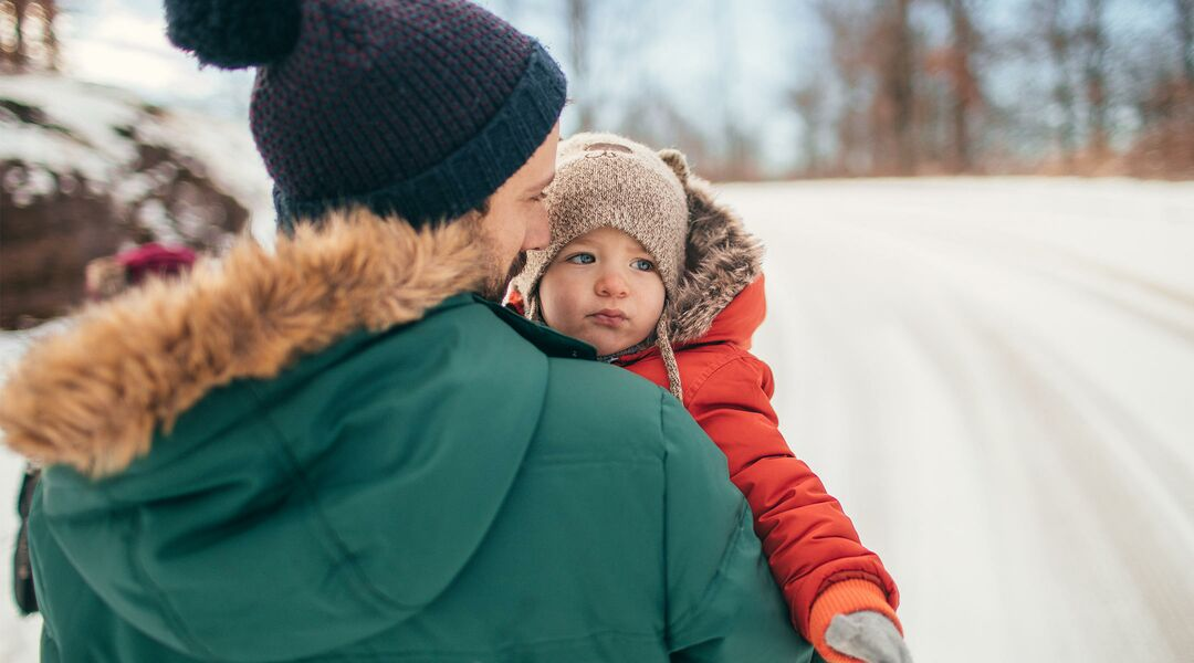 dad carrying baby in winter jacket