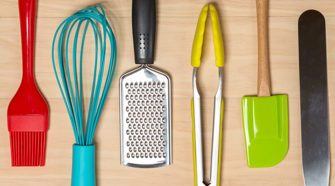 Cooking tools lined up on wooden surface.