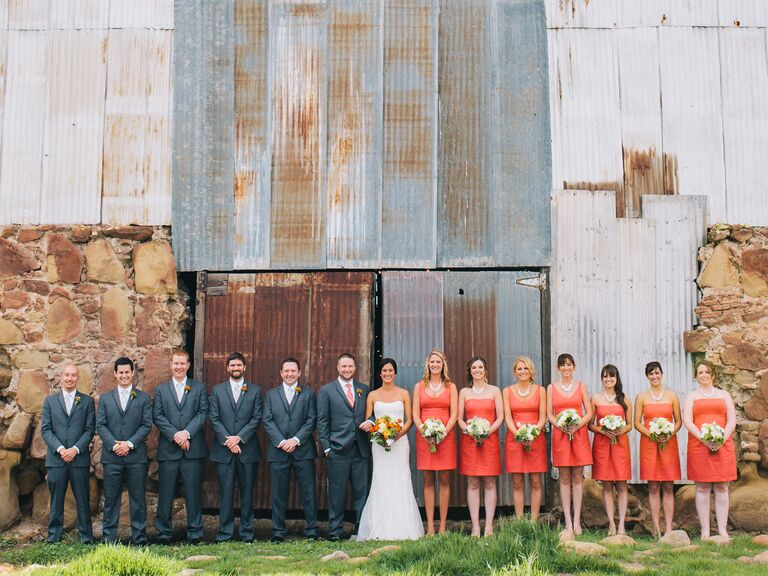 Uneven Coral And Charcoal Wedding Party Lined Up In Front Of A Rusted Barn