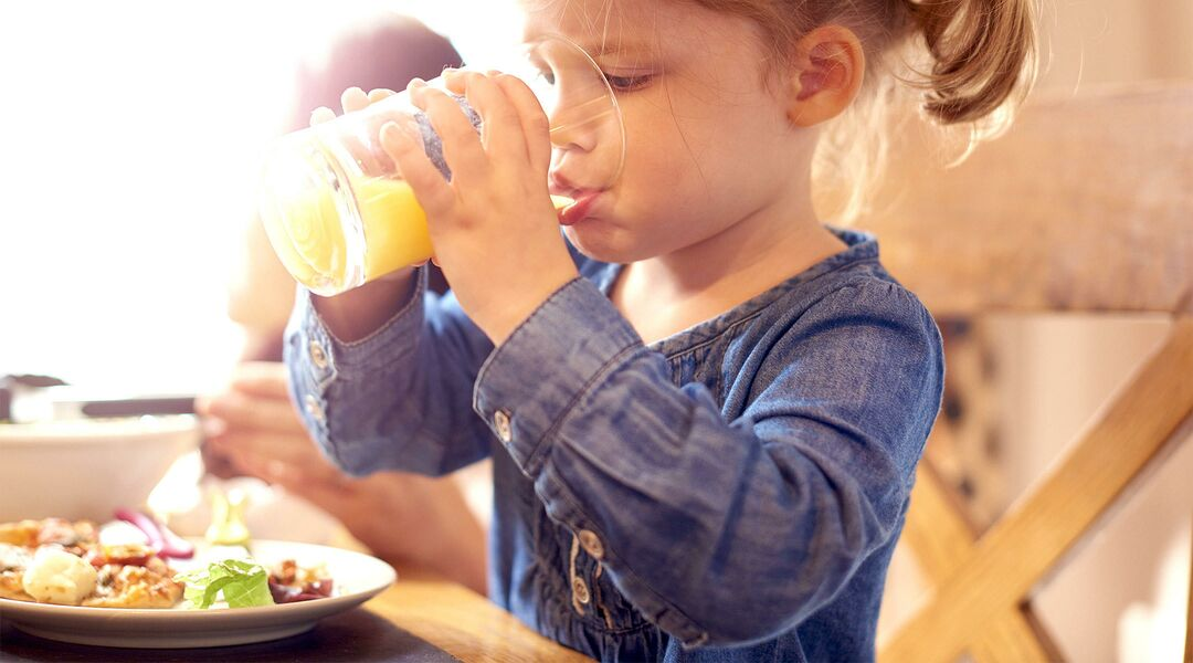 little girl drinking fruit juice from cup