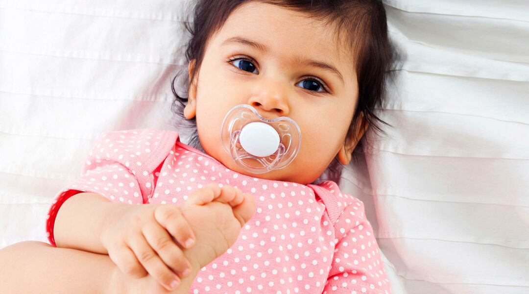 baby laying down with pacifier in mouth