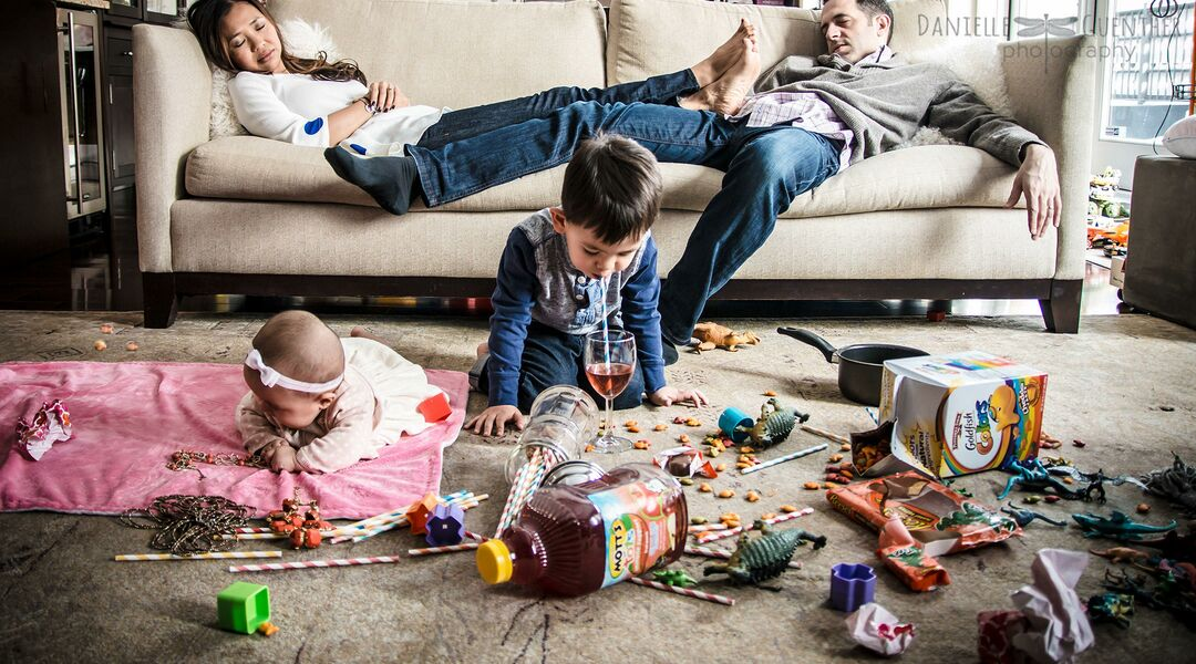 exhausted parents in chaotic mess with children at home