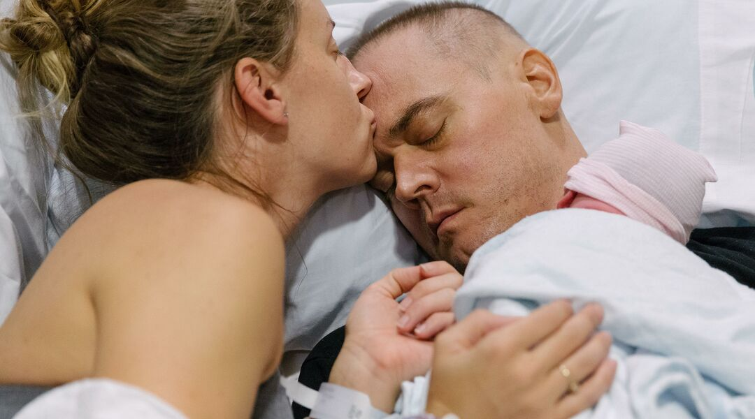 Woman kissing her husband, who has brain cancer, on the forehead as he holds their newborn daughter
