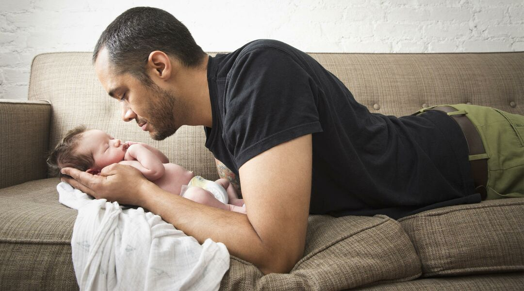 man looking at baby cradled in his hands