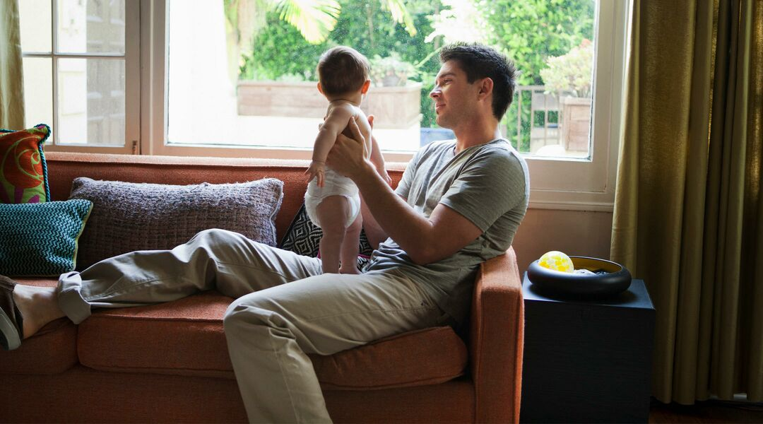 man holding baby on couch