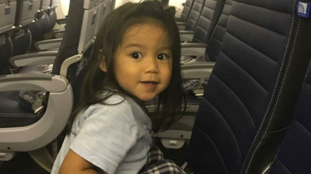 Toddler boy sitting in United Airlines plane seat