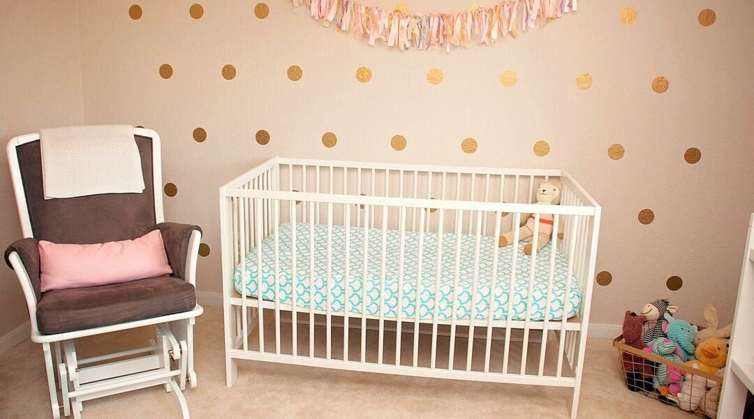 nursery crib and glider with polka dot wall decals