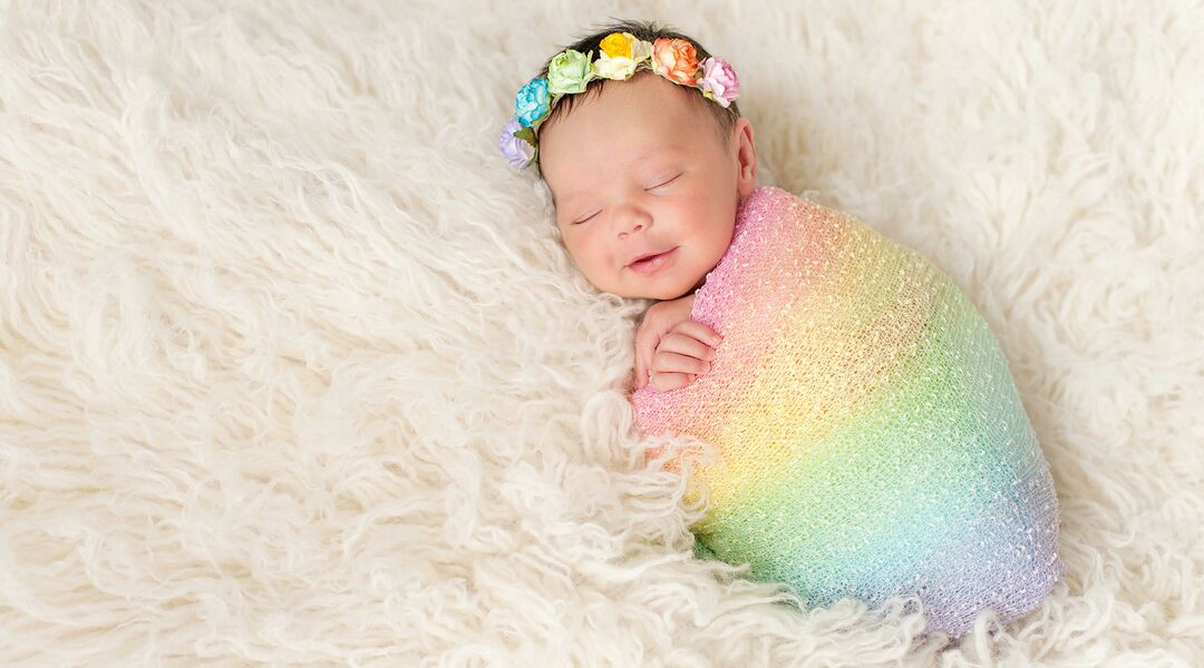 Rainbow baby wearing rainbow blanket