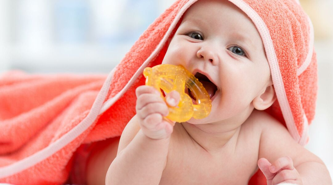Baby chewing on a pretzel teether with a towel on his head