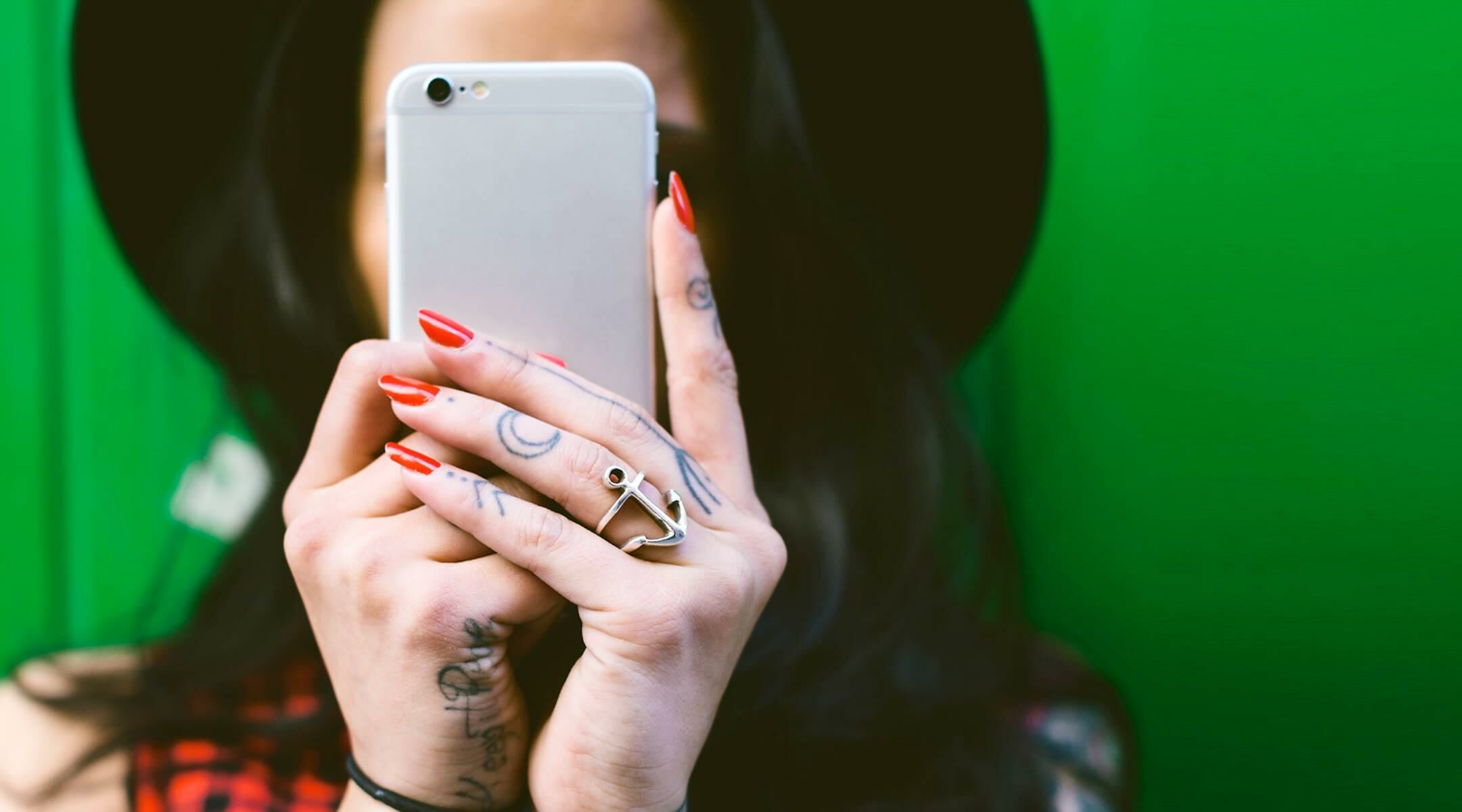 close up of woman holding iphone in front of her face