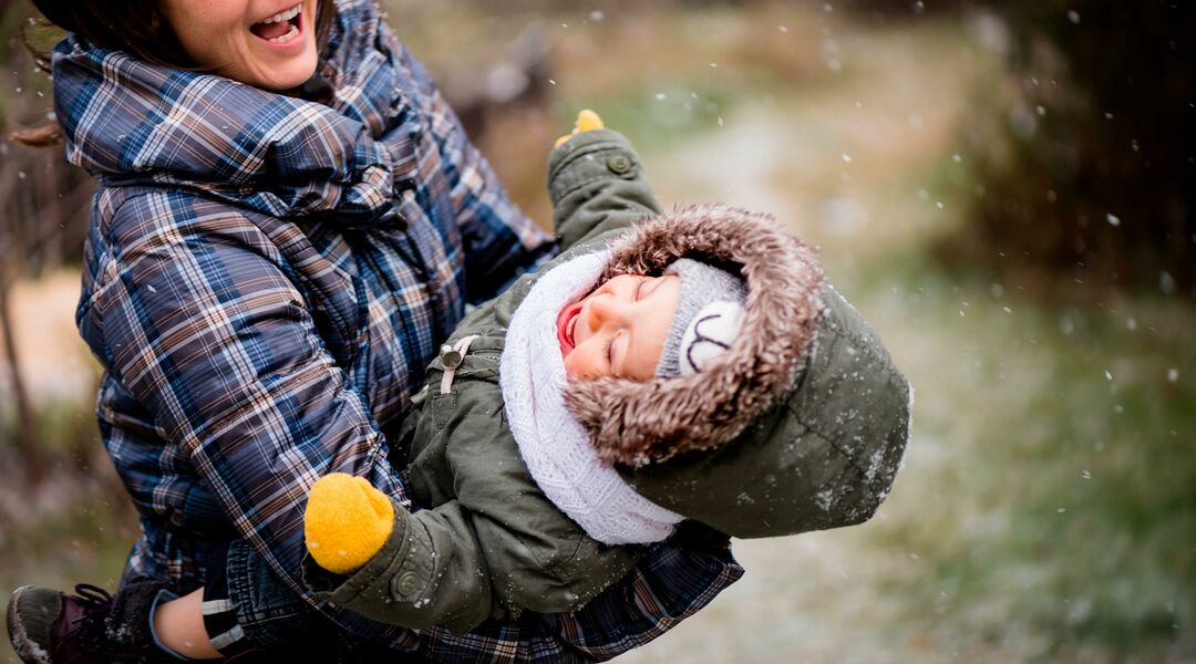 happy mom holding baby during winter in the snow