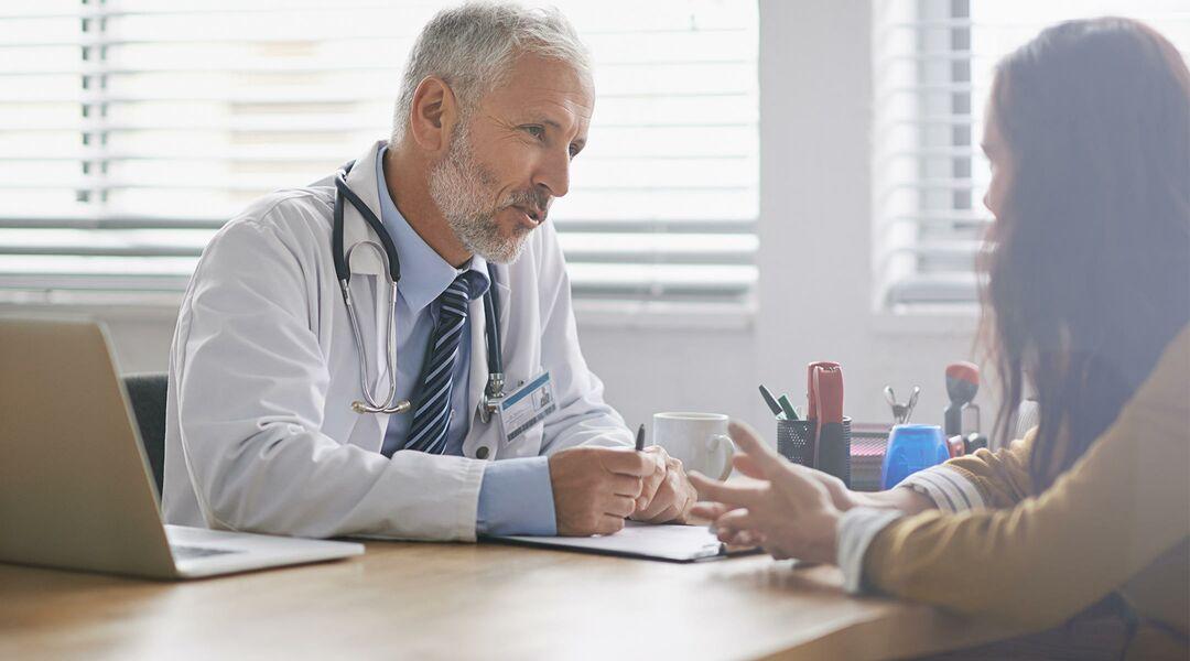 A woman talking to her male doctor across a desk