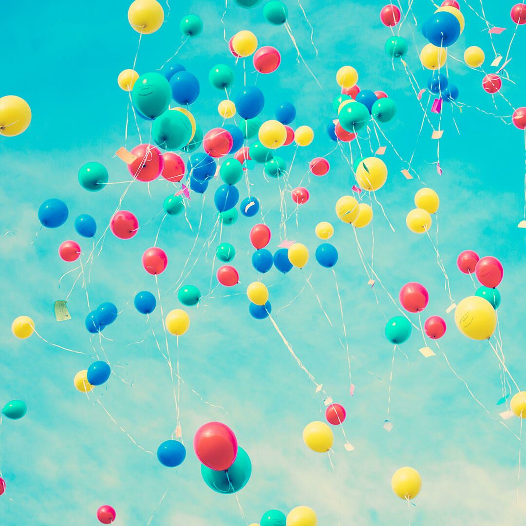 Multicolored balloons floating in a light blue sky