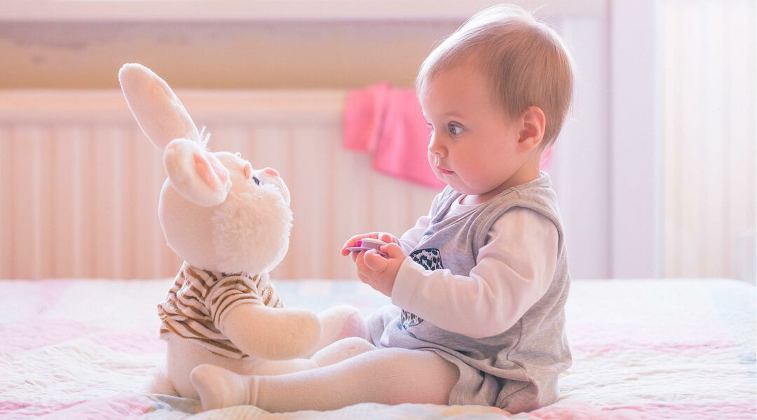 baby on bed sitting across from a stuffed animal bunny