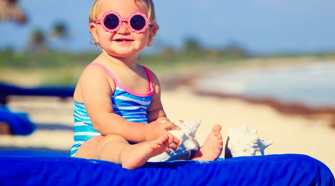 Smiling baby at beach in sunglasses and striped bathing suit.