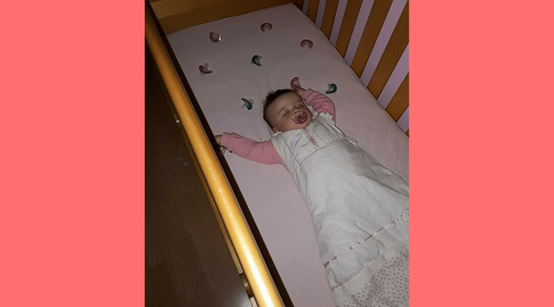 Baby sleeping in crib surrounding by pacifiers