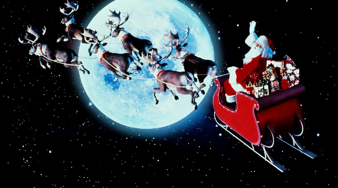 retro image of Santa Claus riding his sleigh past a full moon