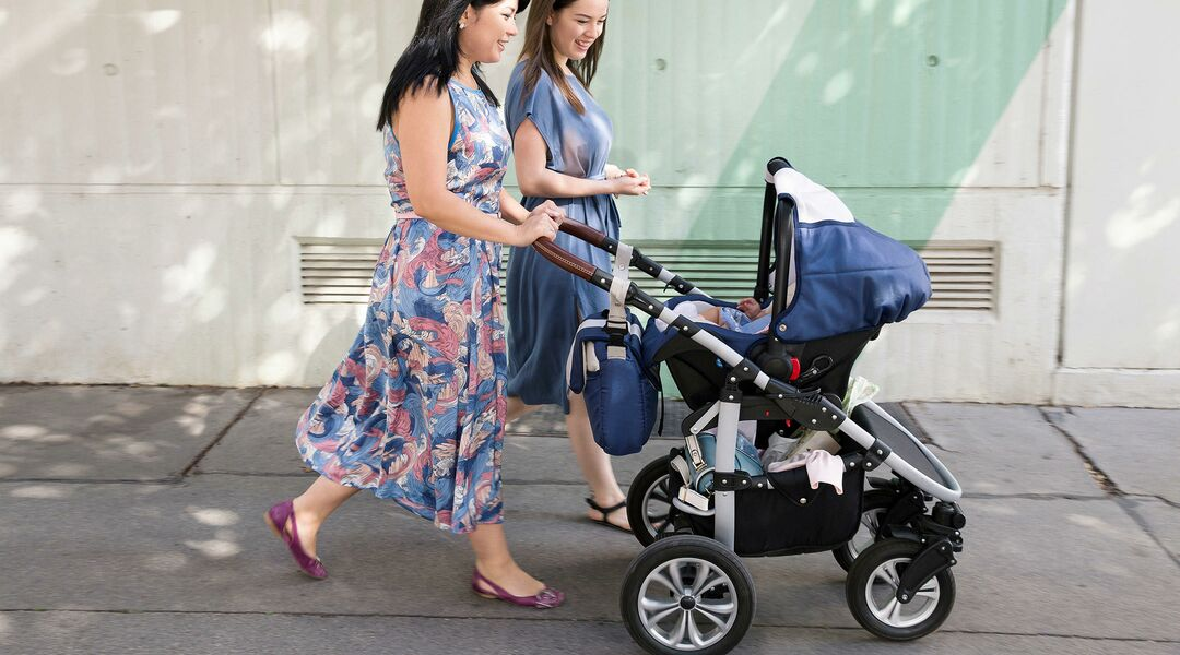 women friends pushing stroller outside together