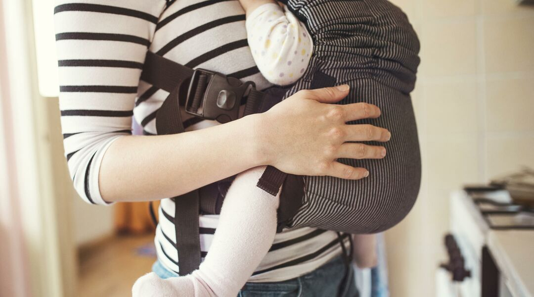 Woman wearing her baby in a baby carrier while standing by a stove
