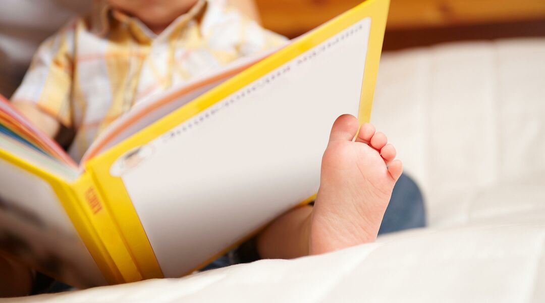 baby reading a book balancing on his foot