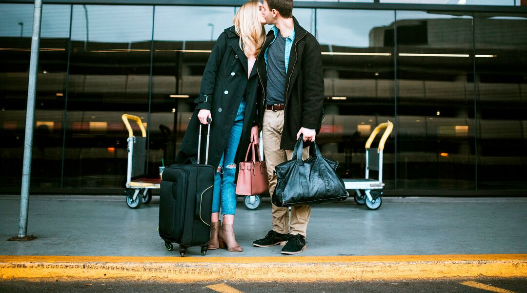 couple kissing at the airport during the holidays