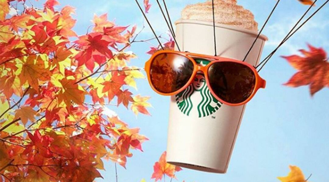 A Starbucks pumpkin spice latte next to foliage