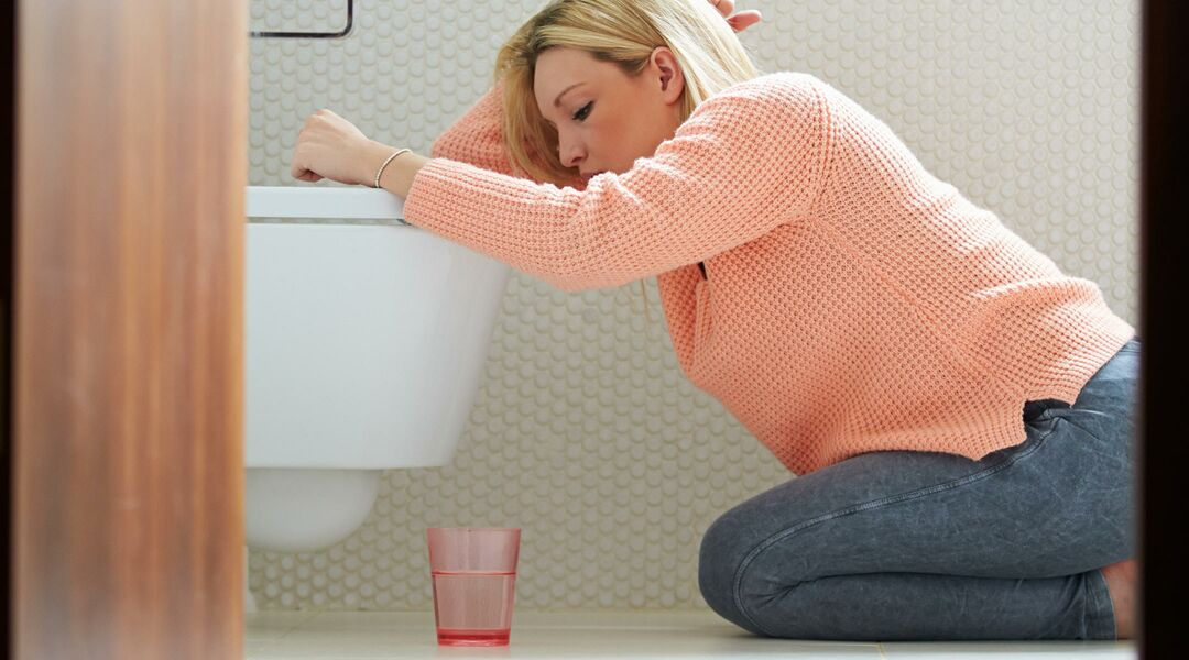 Nauseous woman kneeling in front of toilet