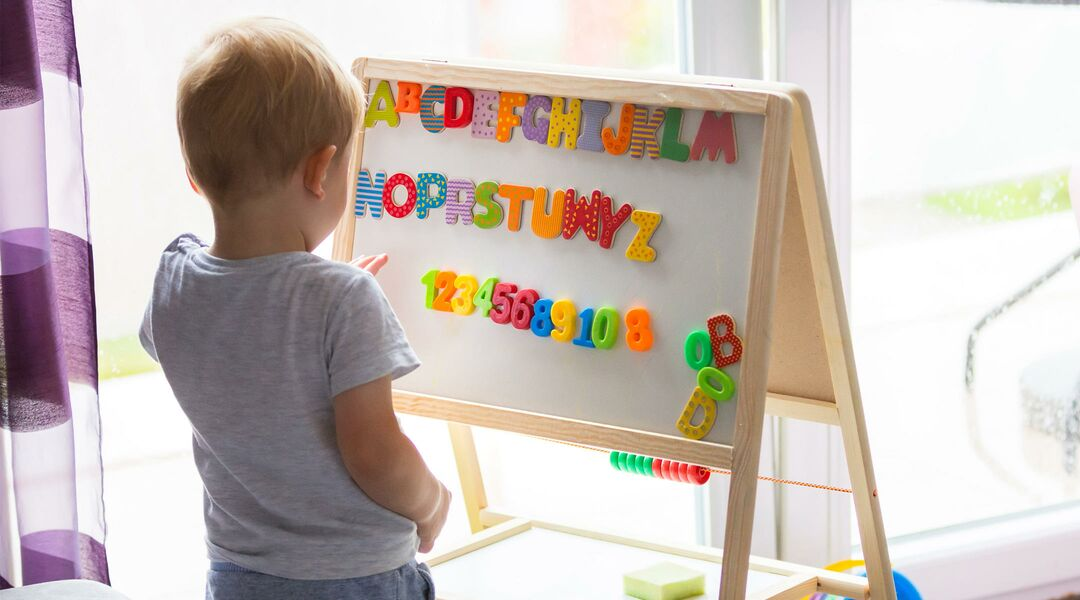 toddler looking at whiteboard with alphabet magnets