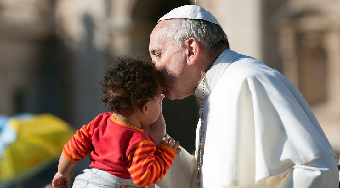 Pope Francis kissing a toddler on the head
