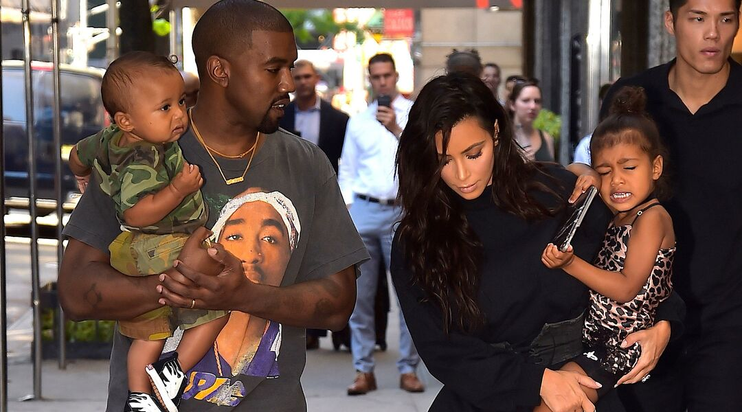 Kim Kardashian and Kanye West carrying Saint and North, who is crying.