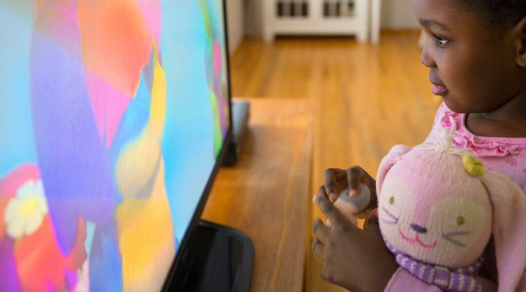 little girl watching tv close up in living room
