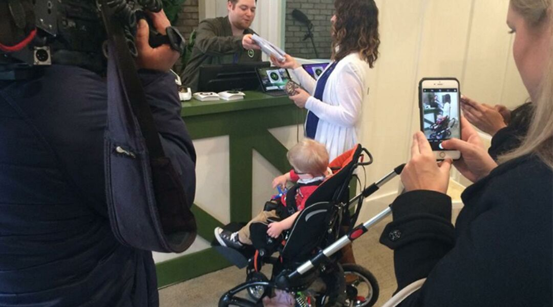 Mother and toddler in stroller buying medical marijuana