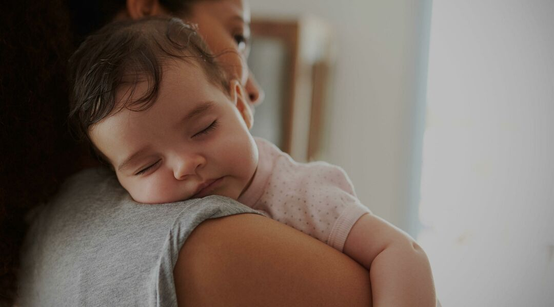 young toddler sleeping on woman's shoulder
