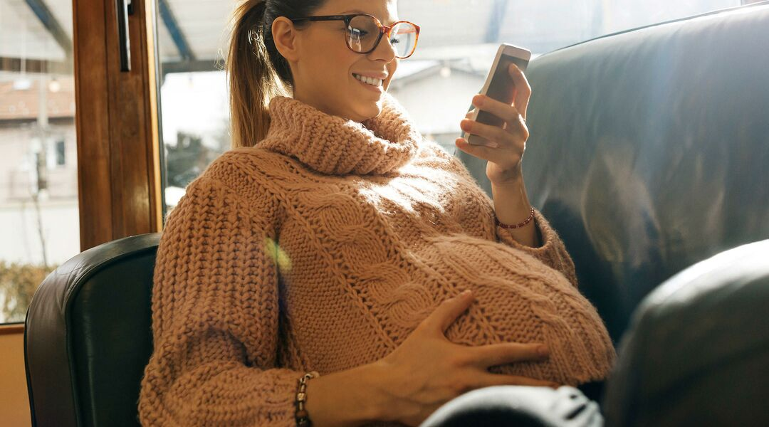 pregnant woman smiling and looking at her phone