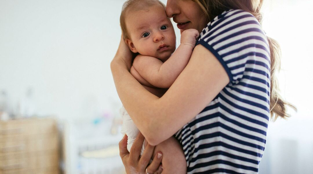 woman holding a baby close to her chest