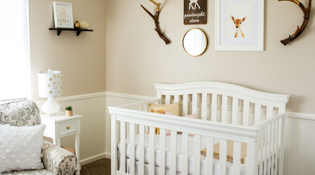 Interior of nursery with deer horns as wall decor and other deer artwork.